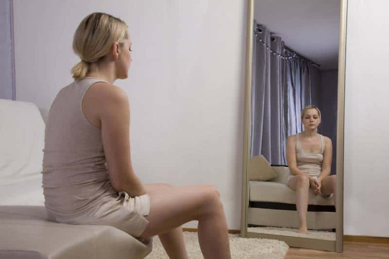 sad woman sitting on bed in front of mirror