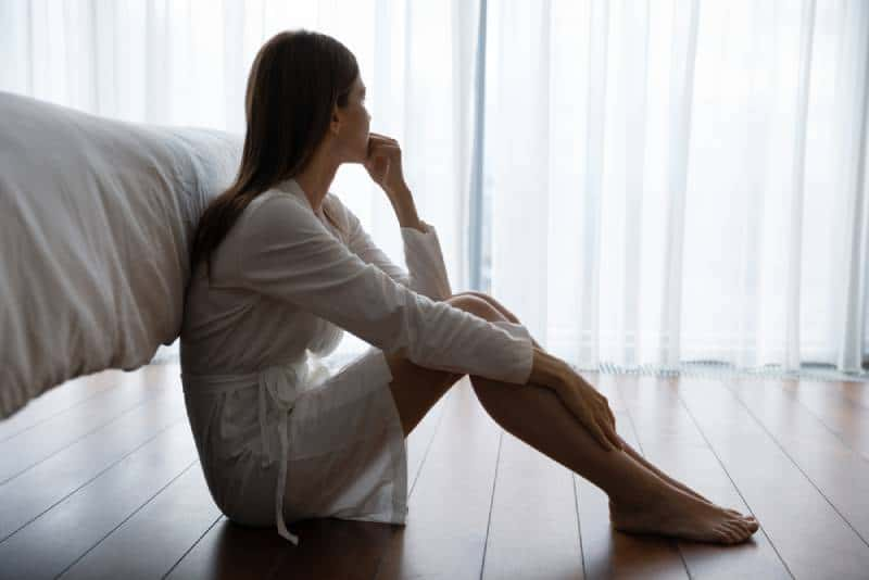 sad woman sitting on floor in bedroom