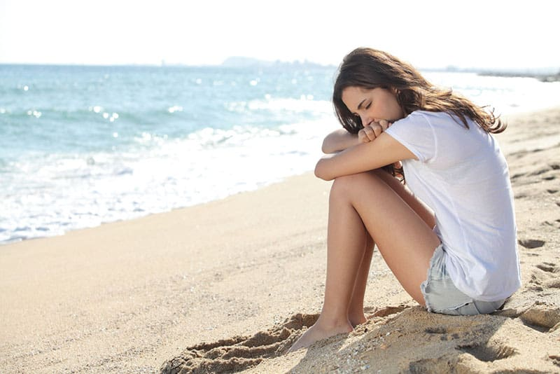 sad woman sitting on the sand by the sea