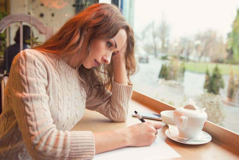 sad woman writing letter at coffee bar