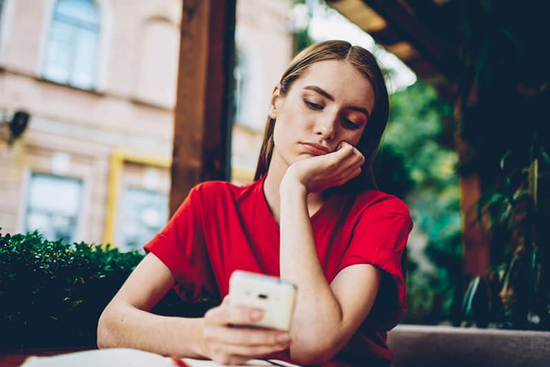 sad young woman with phone