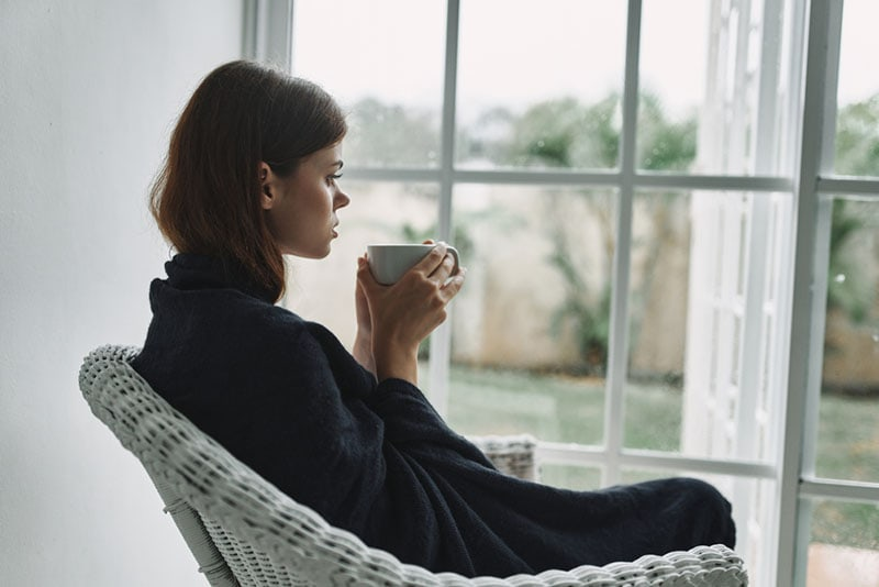 serious woman drinking coffee near the window