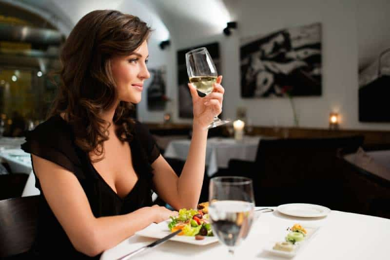 single happy lady at restaurant drinking champange alone