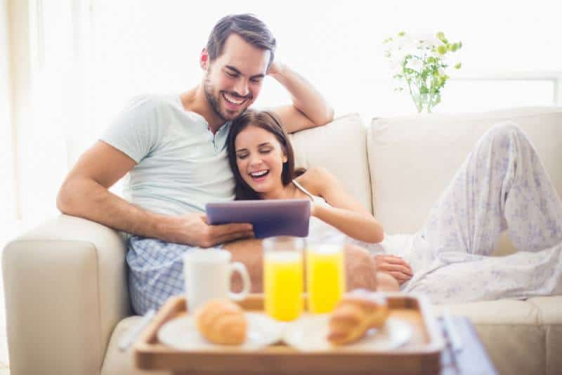 smiling couple at bed typing tablet