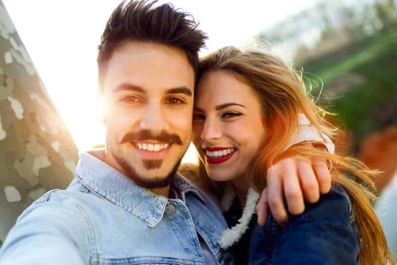 smiling couple taking selfie outside