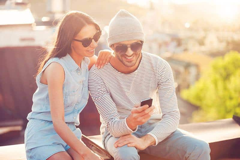 smiling man and woman looking at phone while sitting outside