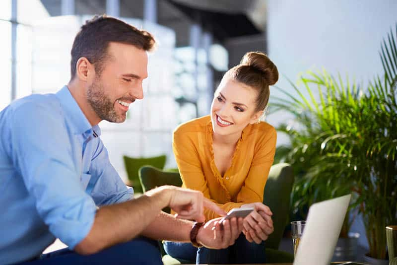 smiling man showing something on his phone to woman