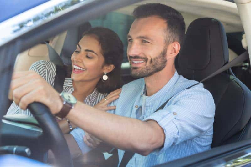 smiling woman hugging her husband while driving car