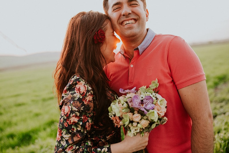 smiling woman hugging smiling man while holding flowers
