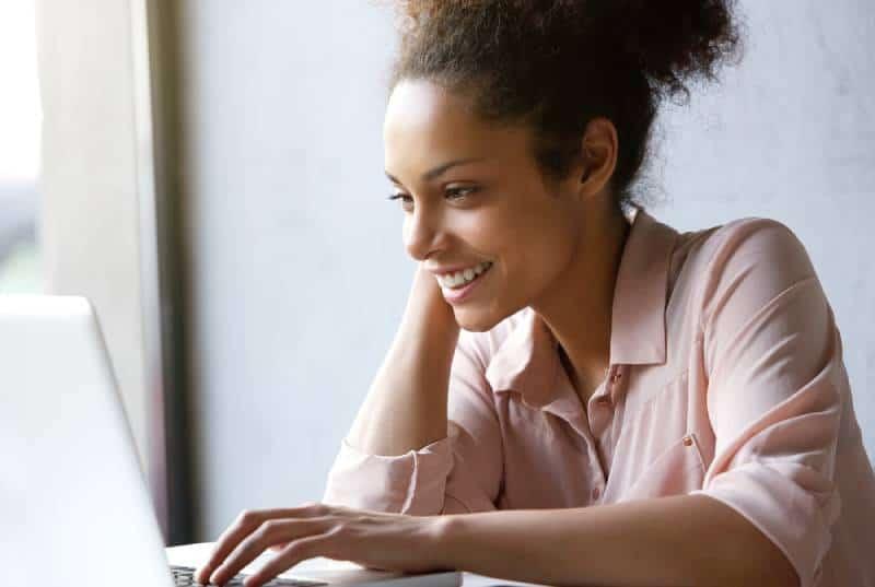 smiling woman looking at laptop screen
