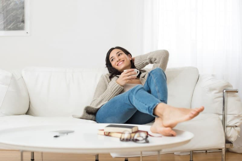 smiling woman sitting at sofa while drinking tea