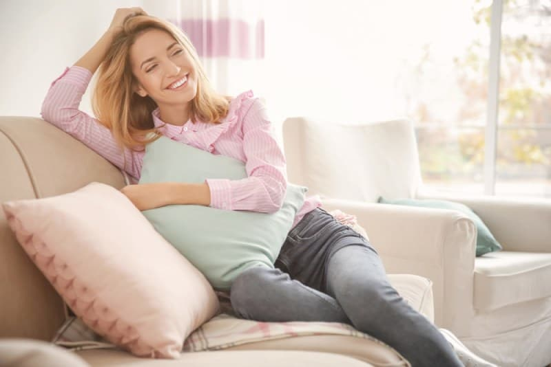 smiling woman with soft pillow at home
