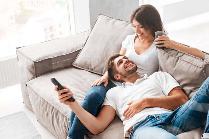 smiling young couple sitting on bed