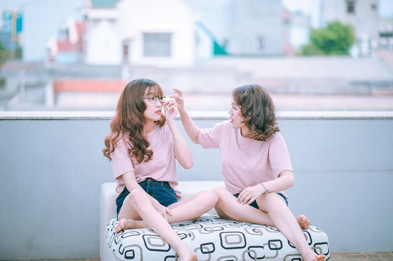 talking with bestfriend both in pink shirts while sitting