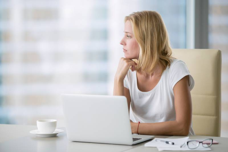 thinking woman at office desk looking outside