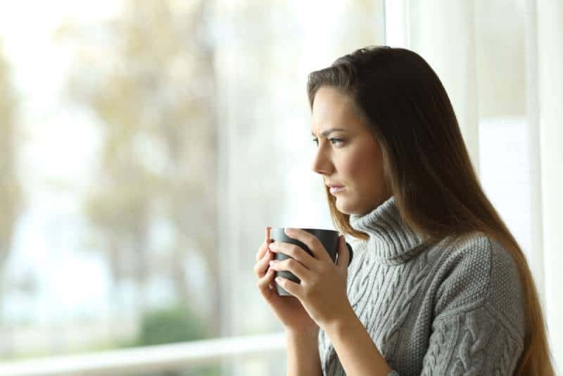 thinking woman holding cup of tea and looking outside
