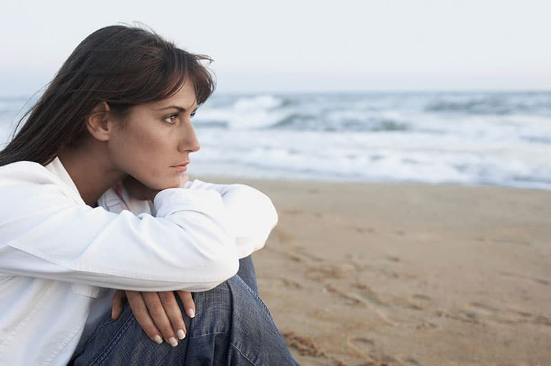 thoughtful woman sitting on the sand
