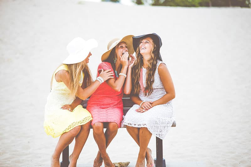 three girls in hats chatting and laughing