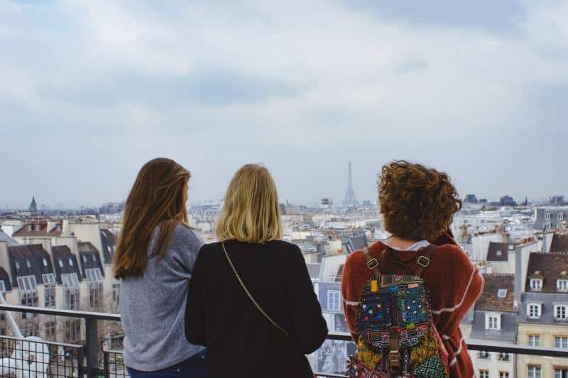 Three young women facing cityscape