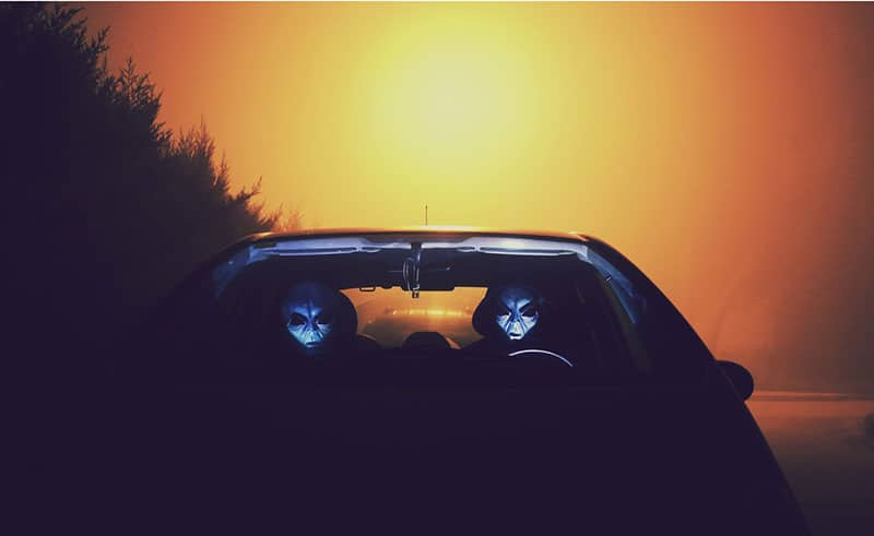 two-alien-inside-car-with dim light background