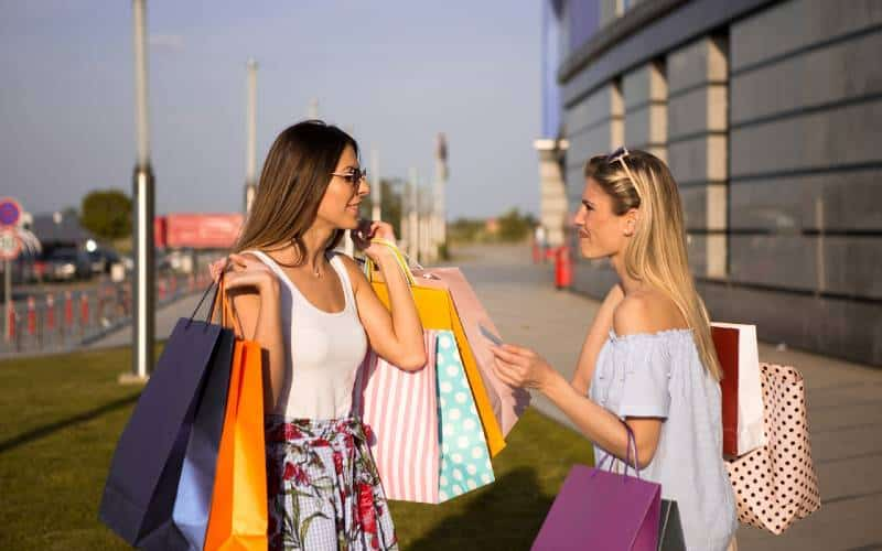 Two women talking on the street while holding paper shopping bags