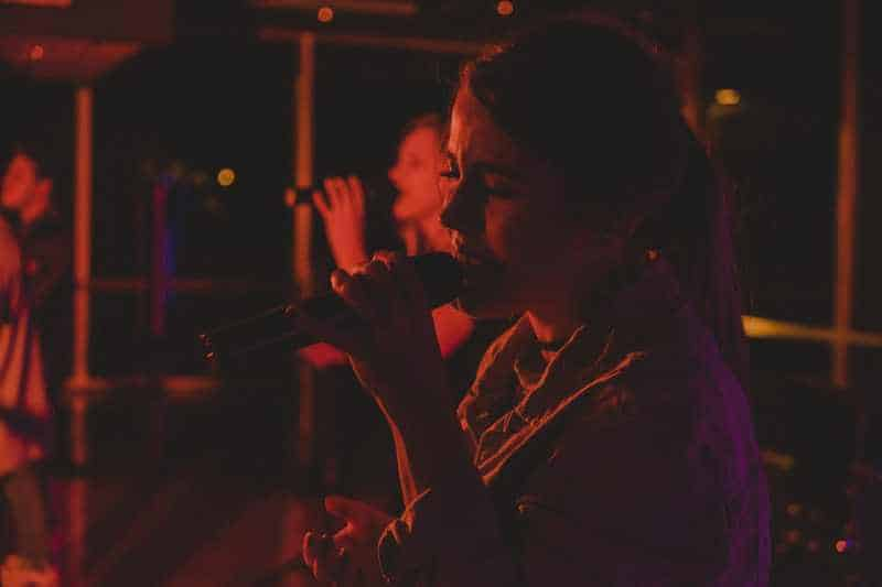 Two women singing on microphones in a room during night time