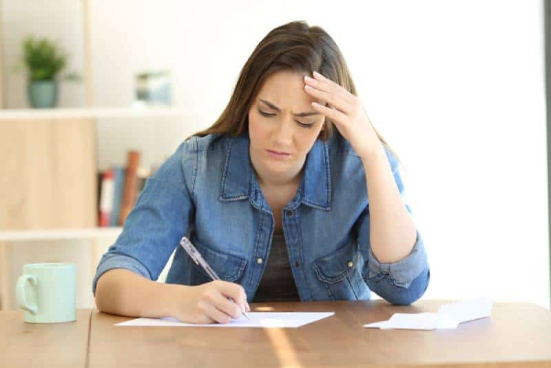 unhappy woman writing a leter at home