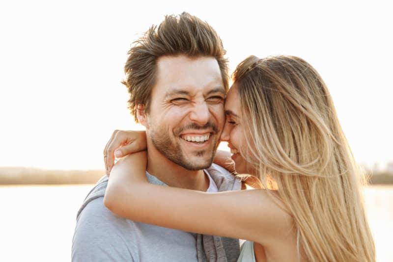 very happy woman around mans neck