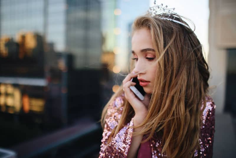 woman with a crown answering a phone