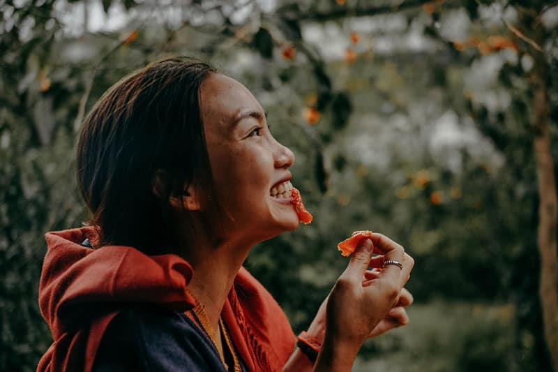 woman-biting-red-fruit on sideview