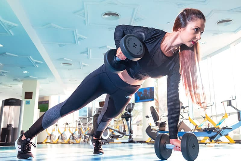 woman exercising in the gym using barbells