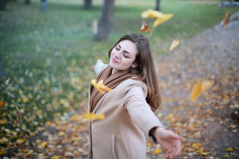 woman in coat feeling the moment with falling leaves