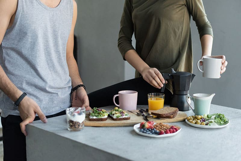 woman holding black mug and guy in gray tank top