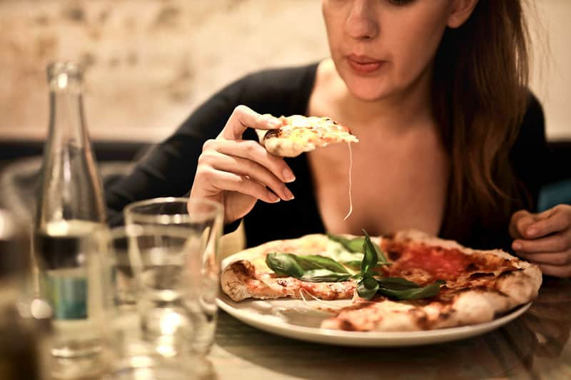 woman holds sliced pizza by the table with glass
