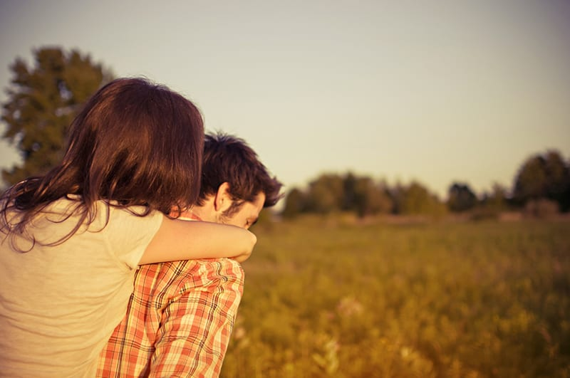 woman hugging man in the field
