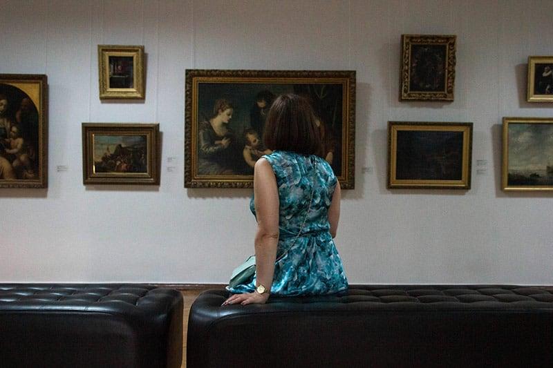 Woman sitting down inside art museum