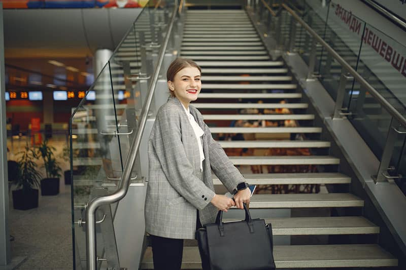 woman inside the airport by the stairs carrying bag