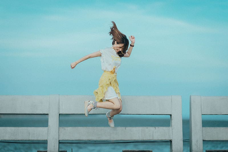 woman in yellow and white dress jump shot