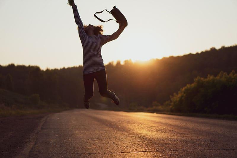 woman jumped for joy on gray asphalt road
