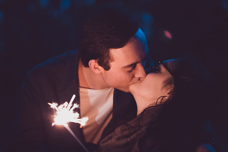 woman kissing man in the night