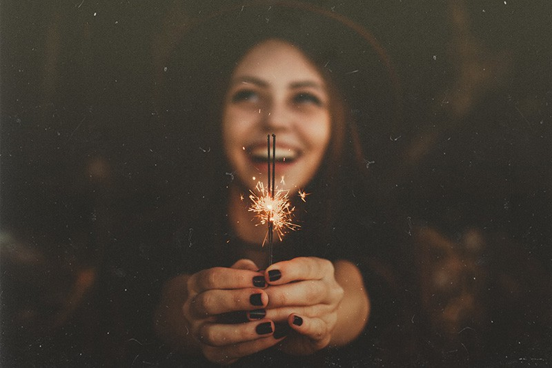 Woman laughing while holding lit sparklers