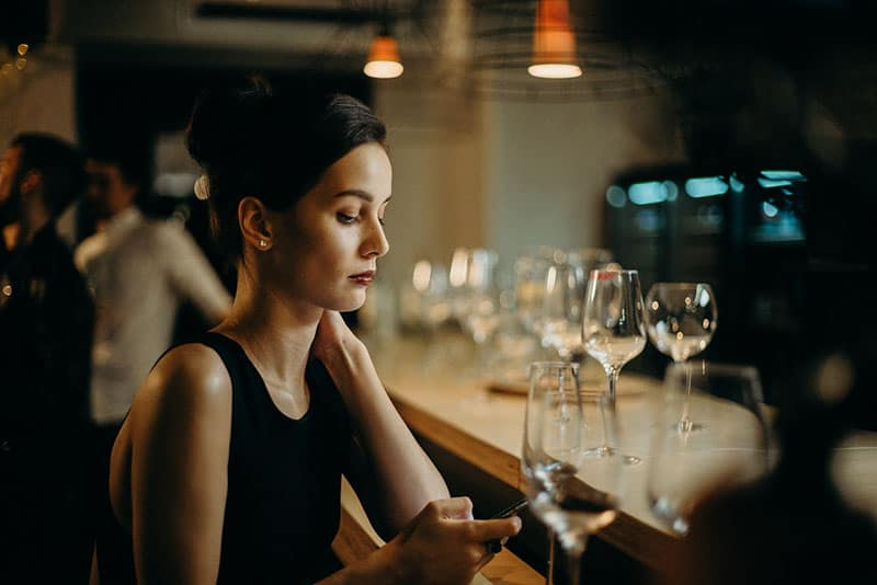 woman in black dress leaning on table texting