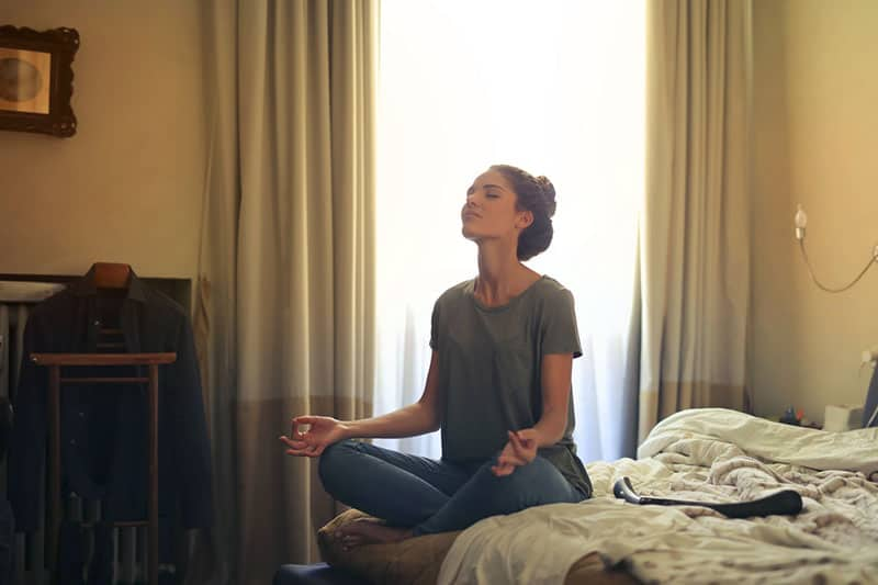 woman meditating in the room on bed
