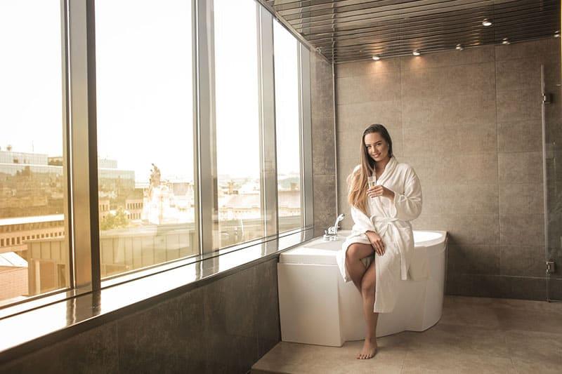 woman on white bathtub and white batchrobe