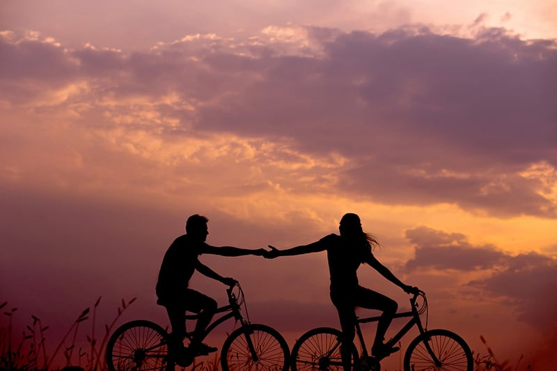 a woman on a bicycle reaches for a mans hand behinde her also on bicycle