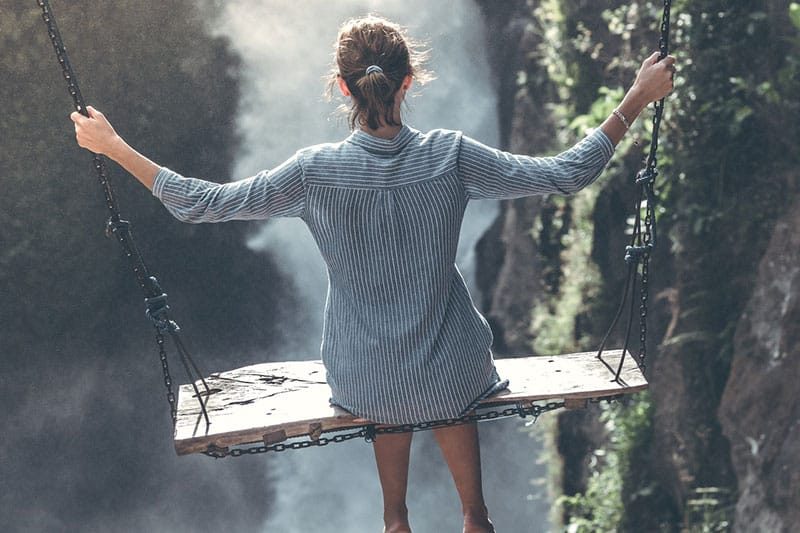 Woman on swing in front of waterfall