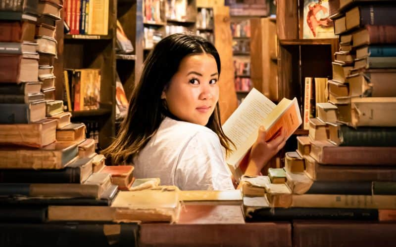 Woman in white top reading in a bookstore surrounded by books
