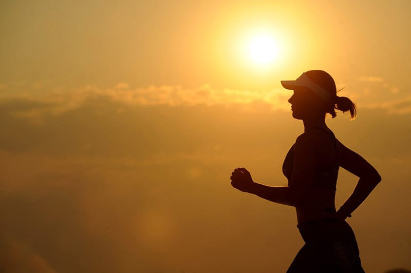 Silhouette of running woman with sunset background