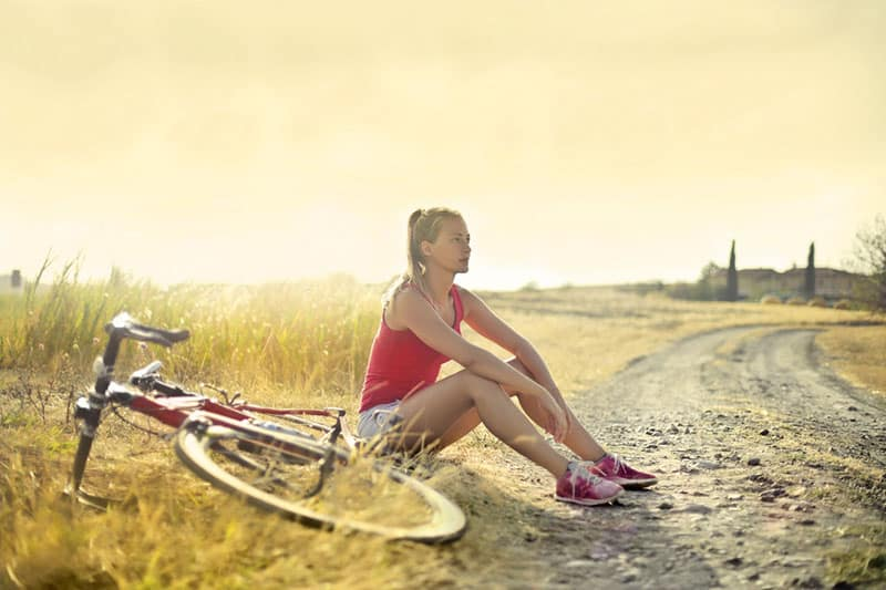 woman -sitting-by-the-side-of-a-dirt and a bike
