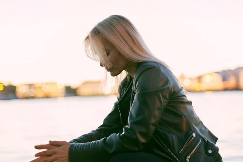 woman sitting near a body of water wearing jacket